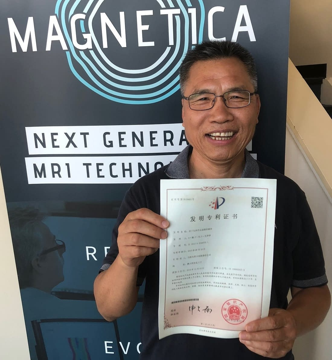 """Dr Riyu Wei, one of the inventors, holding the Chinese Certificate for Magnetica's """"Magnet for Head and Extremity Imaging"""" patent - granted in China and Japan."""
