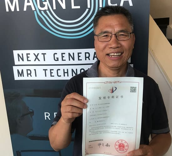 "Dr Riyu Wei, one of the inventors, holding the Chinese Certificate for Magnetica's ""Magnet for Head and Extremity Imaging"" patent - granted in China and Japan."